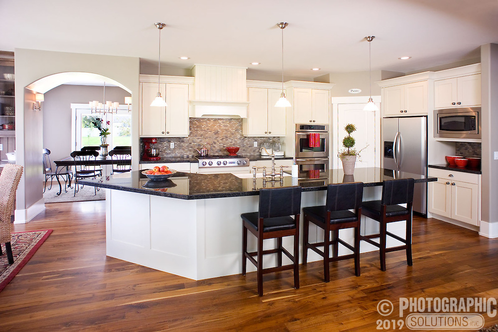 Modern looking kitchen with white cabinets and dark stone countertops.