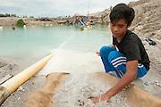 Heri Saputra (13 years) sifts sand in search of tin. Heri is a miner since 1 year and he left school to work here.  <br /> Tin mine on the road to Pemali. Bangka Island (Indonesia) is devastated by illegal tin mines. The demand for tin has increased due to its use in smart phones and tablets.<br /> <br /> Heri Saputra (13 ans) cherche de l'étain. Heri a quitté l'école il y a un an, pour cherher l'étain avec toute sa famille. <br /> Mine d'étain illégale sur la route de Pemali.   <br /> L'île de Bangka (Indonésie) est dévastée par des mines d'étain sauvages. la demande de l'étain a explosé à cause de son utilisation dans les smartphones et tablettes