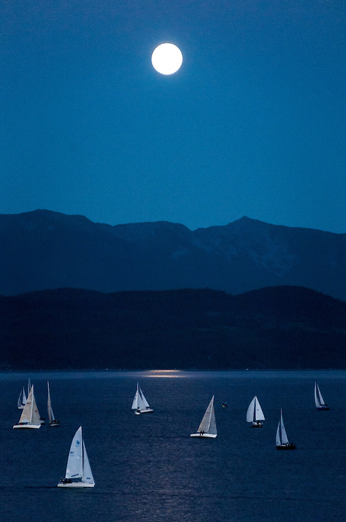 Sailboats on Flathead Lake at night under a full moon with Swan Range visible