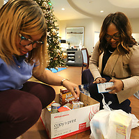 Shay Seals, retail manager at First National Bank in Tupelo and Universal Banker Tinesha Dabbs, pack food for the Salvation Army Build A Box program on Friday morning in Tupelo. The Boxes are to feed a family up to five or more.
