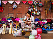 17 MARCH 2017 - KATHMANDU, NEPAL: A vendor sells tourist nick nacks on the plaza in front of Boudhanath Stupa in Kathmandu. She is also making change for people who want to donate money to Buddhist monks. The stupa is the holiest site in Nepali Buddhism. It is also the center of the Tibetan exile community in Kathmandu. The Stupa was badly damaged in the 2015 earthquake but was one of the first buildings renovated.     PHOTO BY JACK KURTZ