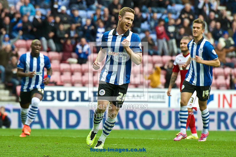 Adam Forshaw of Wigan Athletic (centre) celebrates scoring their first goal from the penalty spot to make it Wigan Athletic 1 Fulham 0 during the Sky Bet Championship match at the DW Stadium, Wigan<br /> Picture by Ian Wadkins/Focus Images Ltd +44 7877 568959<br /> 01/11/2014