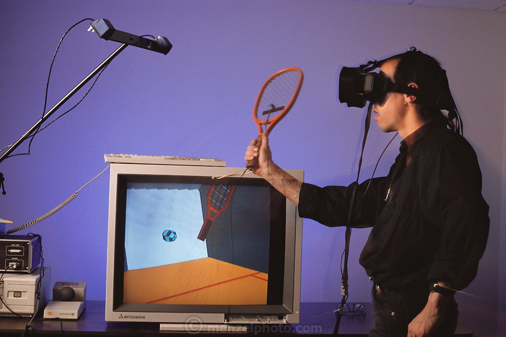 Virtual reality. Cyberspace racquetball game: real strokes made by Christopher Allis, the player are returned by the Cyberspace computer through the virtual, computer- generated environment displayed on the monitor. Admission to this virtual squash court is provided by 3-D video goggles, a magnetic sensor & optical fiber sensors woven into a black rubber glove. The headset sensor transmits data to the computer on the player's position in space, whilst the data glove connects real hand movements to the virtual racquet court. Photo taken at AutoDesk Inc., Sausalito, California. Model Released (1990)