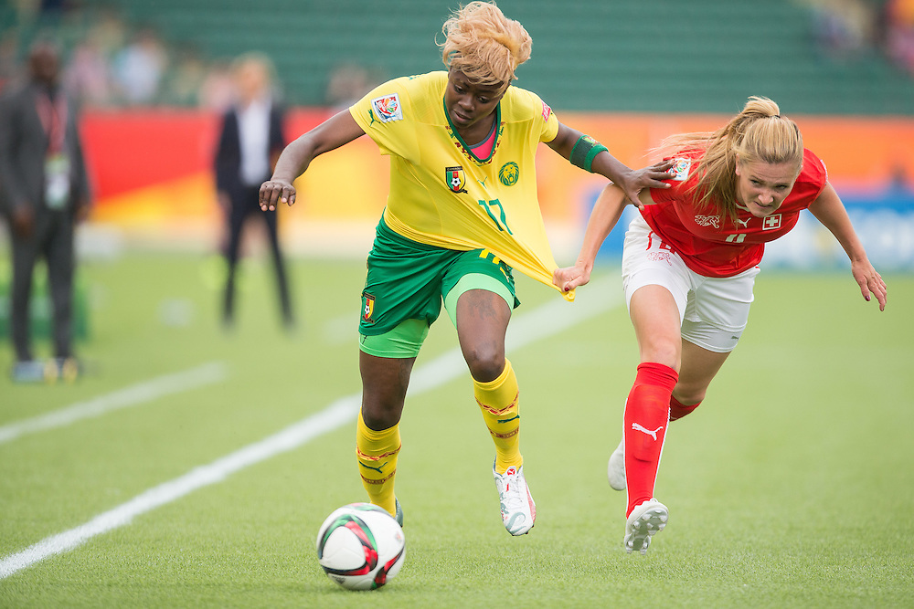 Cameroon's  Gaelle Enganamouit (L) and Switzerland's Rachel Rinast  vie for the ball during the first half of their FIFA Women's World Cup group C match at Commonwealth Stadium in Edmonton, Canada on June 16, 2015.   AFP PHOTO/GEOFF ROBINS