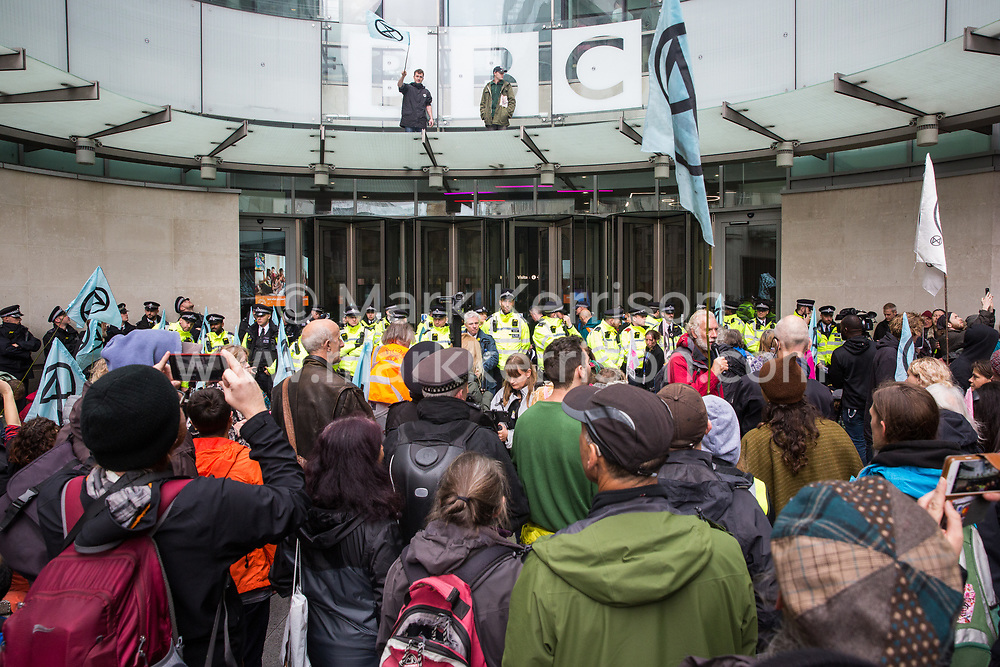 London, UK. 11 October, 2019. Climate activists from Extinction Rebellion, including two above the parapet, block the main entrance to the BBC's New Broadcasting House on the fifth day of International Rebellion protests. They were demanding that the broadcaster 'tell the truth' regarding the climate emergency.