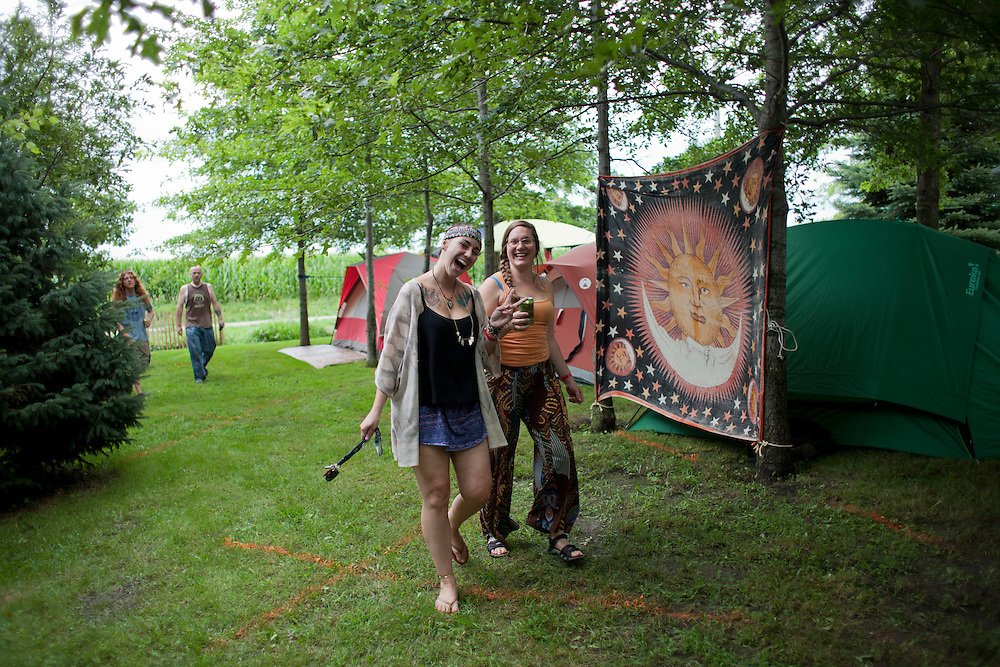 Amanda Mayotte and Angela Huston, both of Cedar Rapids, walk through the leafy camping area at Jerry Hotz's farm north of Lone Tree on Thursday, July 16, 2015. Hotz hosts Camp Euforia, now a three-day music festival featuring a variety of genres from rap to bluegrass and electronic music.
