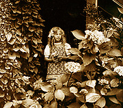French girl in a garden. Circa 1900
