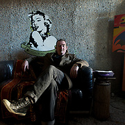 Ireland: Irish artist Frank Buckley seating on a sofa in one of the rooms at his Billion Euro House art installation in central Dublin. ..Worthless euros, taken out of circulation and shredded by Irelands Central Bank, formes the interior walls of an apartment that Mr. Buckley does not own in a building left vacant by the countrys economic ruin...The artist decided to call the apartment  built from thousands of bricks of shredded, decommissioned cash (each brick contains, roughly, what used to be 50,000 euros)  the Billion Euro House. He reckons that about 1.4 billion euros actually went into it, but the joke, of course, is that it is worth simultaneously so much and so little...A large gravestone beside the main door, announces that Irish sovereignty died in 2010, the year that the government accepted an international bailout so larded with onerous conditions that the Irish will be paying for it for years to come. (Paulo Nunes dos Santos/Polaris)
