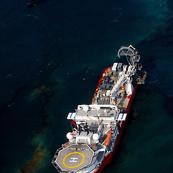 Oil is seen on the surface of the water near a support vessel at the site of the BP Deep Water Horizon oil spill site in the Gulf of Mexico off the coast of Louisiana, U.S., on Saturday, June 19, 2010.  (Mandatory Credit: Derick E. Hingle)
