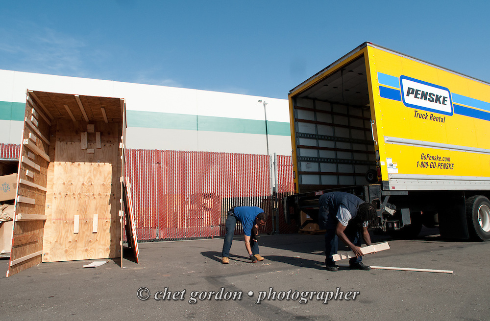 Over the road driver Jose Williams (left) picks up debris near the wooden shipping crate used to protect a custom motorcycle after making deliveries in San Francisco and Sausalito, CA on Wednesday, April 22, 2015. Williams, a cross country trucker with a national household moving company, made several delivery stops in central California's Bay Area during the week with loads from Virginia originating on April 16th.  © Chet Gordon/THE IMAGE WORKS