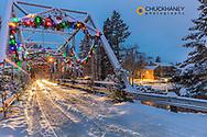 Christmas decorations adorn the historic one lane Swan River Bridge in Bigfork, Montana, USA
