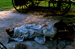 man sleeping on the ground udner blankets by a covered wagon