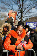 Linda Walker, of Bayshore, New York, (orange jacket) contemplates as Barack Obama is sworn in as president of the United States.