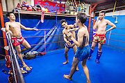 "18 DECEMBER 2104 - BANGKOK, THAILAND: An informal workout and sparring session at the Kanisorn gym. The Kanisorn boxing gym is a small gym along the Wong Wian Yai - Samut Sakhon train tracks. Young people from the nearby communities come to the gym to learn Thai boxing. Muay Thai (Muai Thai) is a Thai fighting sport that uses stand-up striking along with various clinching techniques. It is sometimes known as ""the art of eight limbs"" because it is characterized by the combined use of fists, elbows, knees, shins, being associated with a good physical preparation that makes a full-contact fighter very efficient. Muay Thai became widespread internationally in the twentieth century, when practitioners defeated notable practitioners of other martial arts. A professional league is governed by the World Muay Thai Council. Muay Thai is frequently seen as a way out of poverty for young Thais and Muay Thai camps and schools are frequently crowded. Muay Thai professionals and champions are often celebrities in Thailand.     PHOTO BY JACK KURTZ"
