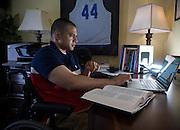 Afganistan war vet Josh Himan works on his computer at his family's home in Woodbridge, VA.