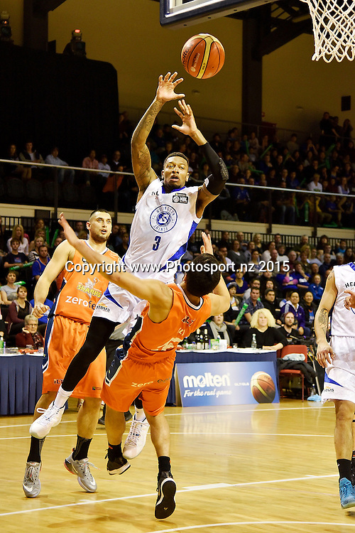 Torrey Craig of the Saints jumps to shoot with Shea Lli of the Southland Sharks in defence during the NBL final basketball match between Wellington Saints and Southland Sharks at the TSB Arena in Wellington on Sunday the 5th of July 2015. Copyright photo by Marty Melville / www.Photosport.nz