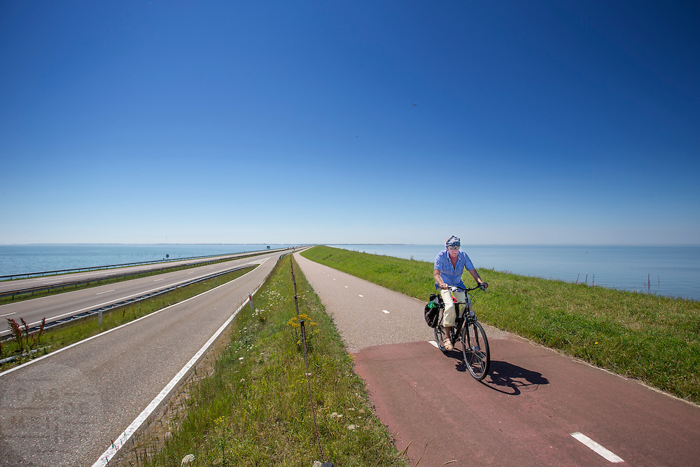 Fietsers rijden over de Afsluitdijk. In 1932 werd de opening tussen de Waddenzee (rechts) en de toenmalige Zuiderzee gesloten. Nu is het een belangrijke verkeersader tussen Friesland en Noord-Holland en scheidt het de Waddenzee met het IJsselmeer.<br /> <br /> Cyclists are riding on the Afsluitdijk. In 1932, the gap between the Wadden Sea and the former Zuiderzee closed by the Afsluitdijk. Now it is a major thoroughfare between Friesland and North Holland and it separates the Wadden Sea from the IJsselmeer.