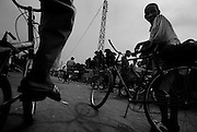 The city of Koundarà street scene, kids riding bikes.