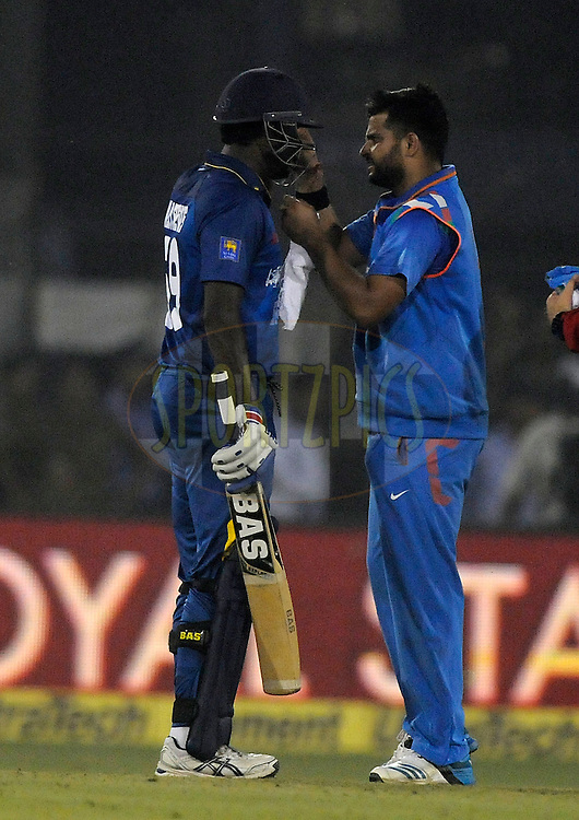 Suresh Raina of India helps Angelo Mathews captain of Sri Lanka during the 1st One Day International, ODI, between India and Sri Lanka held at the Barabati Stadium, Cuttack, India on the 2nd November 2014<br /> <br /> Photo by:  Pal Pillai/ Sportzpics/ BCCI