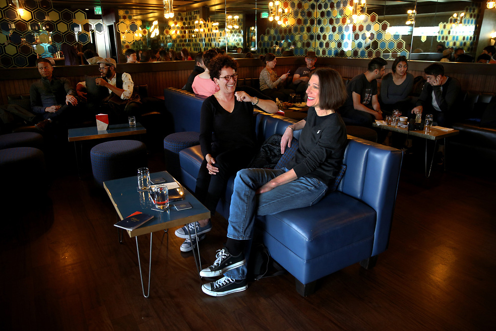 From center left: Gizelle Cadogan and Cynthia Antonion chat over a drink at The Beehive, Saturday, May 5, 2018, in San Francisco, Calif. The Beehive is located at 842 Valencia Street.