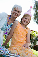 Grandmother with granddaughter in garden while birthday party
