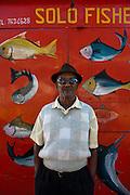 Mauritius. Man at fish stall.