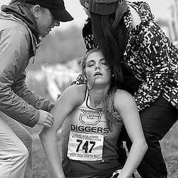 Volunteers help Hanna Larson, from Sugar-Salem High School to her feet after she collapsed after crossing the finish line of the Girls 3A Idaho State Cross Country Championship held at Eagle Island State Park. Larson finished in 19th place with a time of 21:37.7. Saturday November 1, 2014