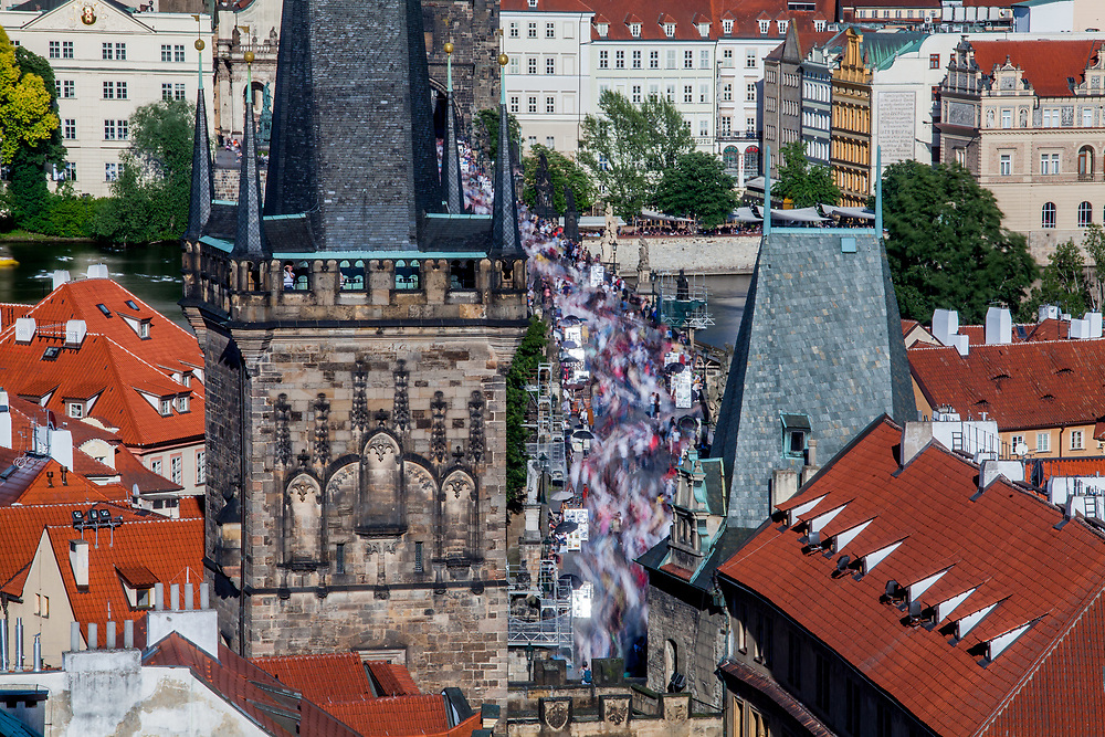 A detail with crowds moving across Charles Bridge seen from the Lesser Town (Mala Strana) Bridge Towers towards the city center.