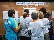 07 AUGUST 2016 - BANGKOK, THAILAND: People look for their names on voting rolls at a polling place at Wat That Thong in Bangkok. Thais voted Sunday in the referendum to approve a new charter (constitution) for Thailand. The new charter was written by a government appointed panel after the military coup that deposed the elected civilian government in May, 2014. The charter referendum is the first country wide election since the coup.      PHOTO BY JACK KURTZ