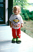 Toddler age 2 smiling wearing mother's shoe's.  Cedarville Michigan USA