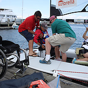 Skipper Sarah Everhart Skeels, Tiverton, RI, is helped into the boat by Mike Pinckney and Brian Todd  before sailing with Cindy Walker, (right), Middletown, RI, the only all female team competing in The Skud 18 class, during the C. Thomas Clagett, Jr. Memorial Clinic & Regatta at Newport, Rhode Island hosted by Sail Newport at Fort Adams. <br /> The Clagett is North America's premier event for sailors with disabilities with sailors competing in the 3 Paralympic class boats and is an integral part of preparation for athletes preparing for  Paralympic and world championship racing. Newport, Rhode Island, USA. 26th June 2015. Photo Tim Clayton