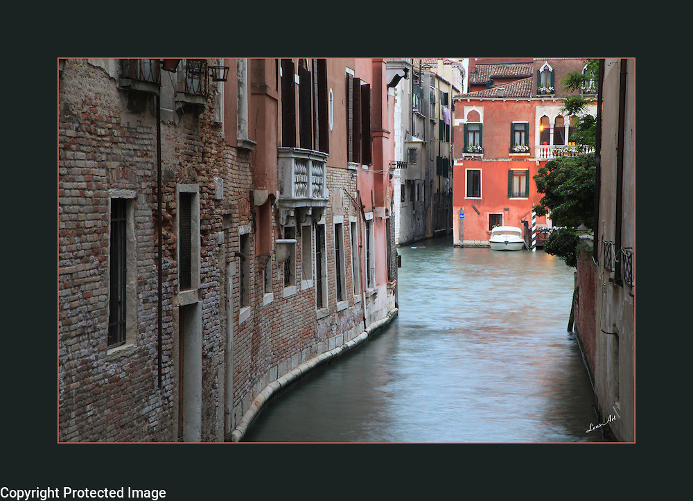 A canal in Venice with leading line on left quickly brings the eye to the pastel building at right.