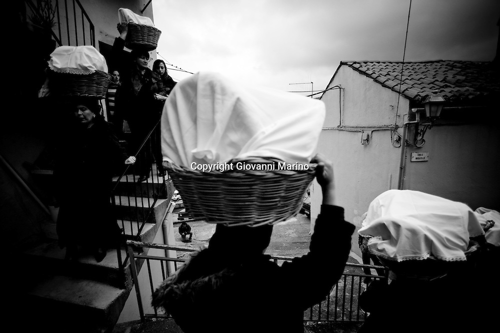 "Verbicaro/Calabria/Italy 20-03-08 - Ritual of the ""Battenti"". The Procession of the bread. On the night of Holy Thursday Verbicaro stages the traditional rite of Battenti, which dates back to 1473. Initially characterized by ""the rite of the first blood"", which means the protagonists beat their legs vigorously with their hands until they become red. Then, with a tool cork ""cardillo"" which has embedded pieces of glass, they start to beat themselves and the first blood flows. As the blood flows, a man carrying a bottle to his lips, blows wine into the wounds...When everyone has his legs covered with blood, they start to run with hands crossed on the chest. Three times they circle the old town stopping in front of churches. They leave as a group but it is not a procession, each runner has their own route and the streets may differ. The event takes place between Thursday  and Friday  (between midnight and 02.00). At 4.00 (approx.) in the morning there is a solemn procession with living statues and paintings."