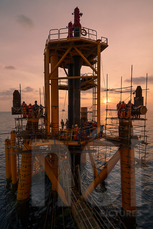 Workers building a structure on an oil rig offshore of Vung Tau, Vietnam, Southeast Asia