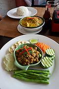 Phnom Penh, Cambodia. Khmer Saravan Restaurant with traditional Cambodian cuisine. Banana Flower Salad (backgr.), Khmer Amok (m.)