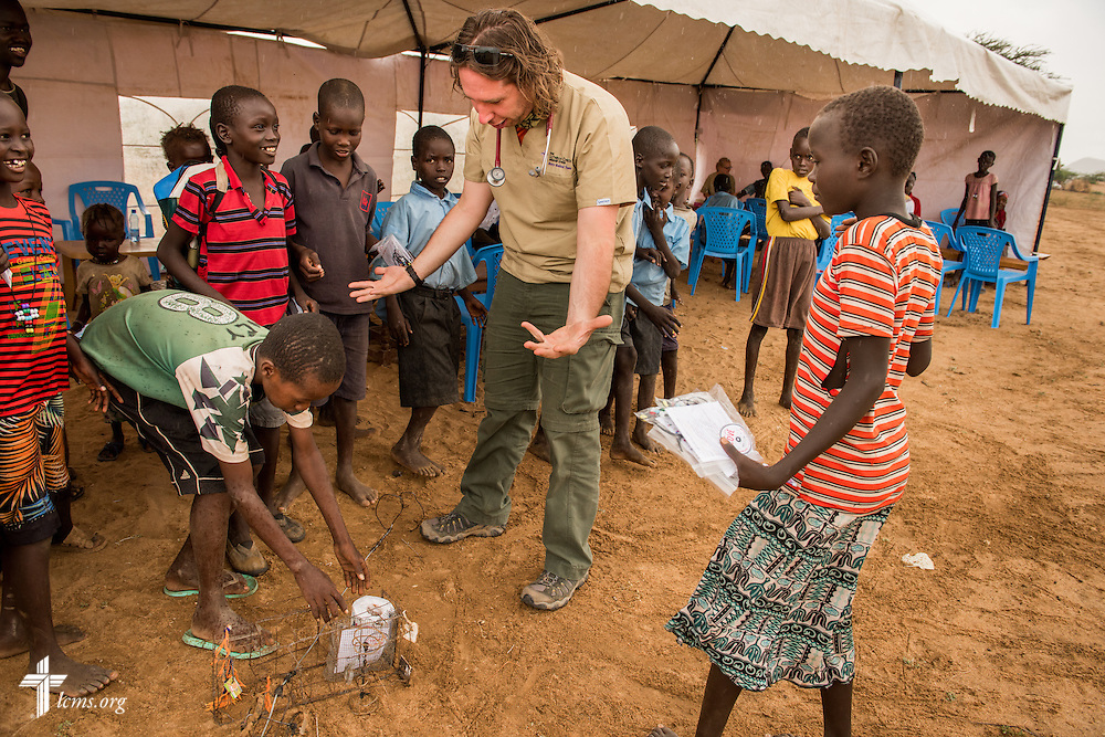 Christopher Curtis, a travel nurse from St. Louis, plays with children during a break at the LCMS Mercy Medical Team on Tuesday, June 21, 2016, in Nataparkakono, a village in Turkana, Kenya.  LCMS Communications/Erik M. Lunsford