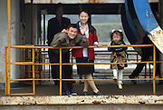 A North Korean family wave to a Chinese tourist boat on the Yalu River border town of Sunuiju, DPRK October 10, 2006. North Korea declared that it has conducted an underground nuclear test ó becoming only the eighth country to do so.  DPRK, north korea, china, dandong, border, liaoning, democratic, people's, rebiblic, of, korea, nuclear, test, rice, japan, arms, race, weapons, stalinist, communist, kin jong il