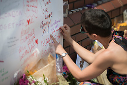 © Licensed to London News Pictures. 20/06/2017. London, UK. A woman writes a message on a banner placed on a wall outside Finsbury Mosque in north London after a van ploughed into a crowd nearby. One person has been killed and 10 people are injured. Darren Osborne, 47, from Cardiff, continues to be held on suspicion of attempted murder and alleged terror offences.  Photo credit: Peter Macdiarmid/LNP