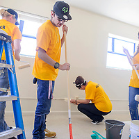 Joey Baldonado, center, Annyssa Baldonado and a group of other volunteers repaint a bedroom at Battered Families Services in Gallup Saturday.