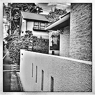Private surveillance encroaching upon the public space: Although a security camera of a newly built house is pointed in the direction of the front door, in Tokyo's tightly packed suburbs the camera clearly captures passersby on the public street.  Tokyo, Japan.