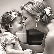 Black and white photo of bride kissing cute little flower girl