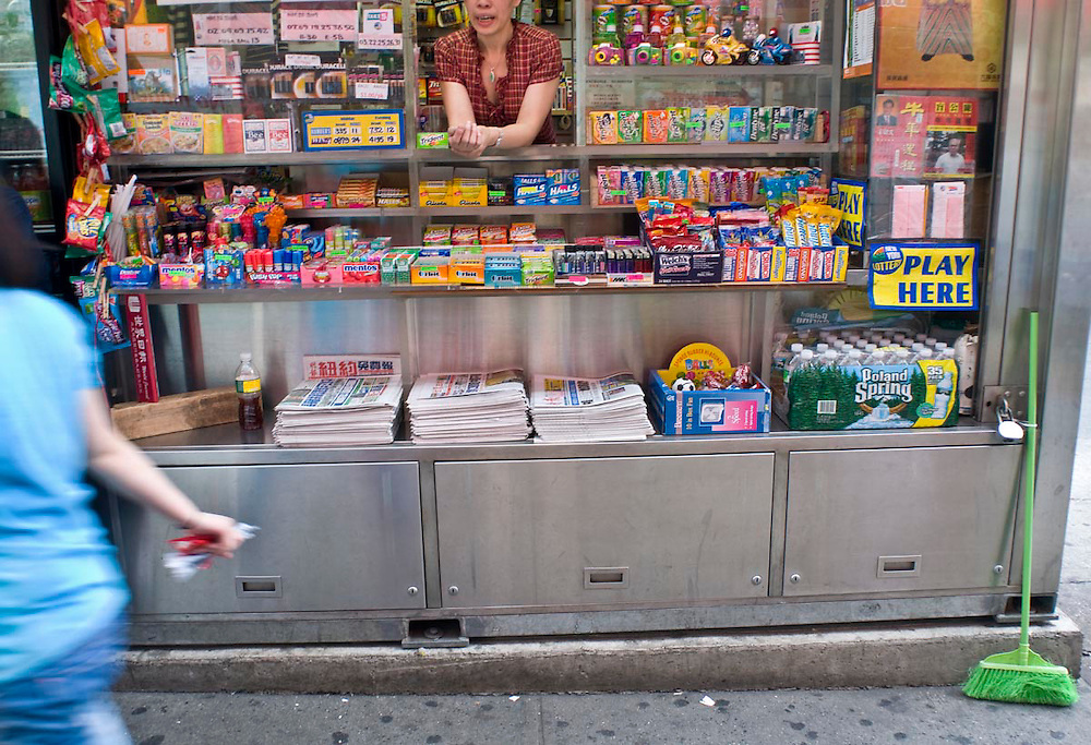 An Asian woman walks past a street vendor's newstand in China Town, NYC.