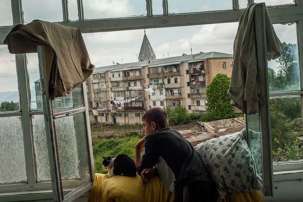 A young man, with a cat, looks out of the window of his mother's apartment in Shusha during his last summer holiday before joining the Military School in Yerevan. Nagorno Karabakh