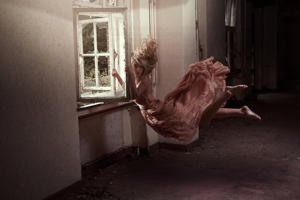 Conceptual image of female floating at an old window