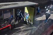 Young pedestrians pass-by a bus stop ad, on 11th March 2019, in London, England.