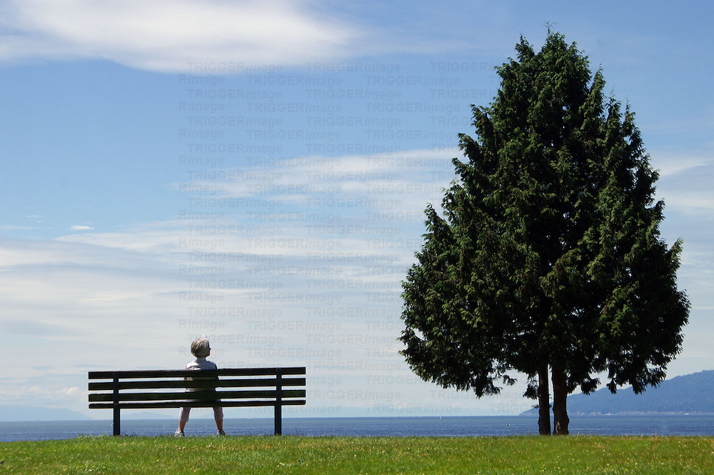 Woman sitting on a bench looking at the sea view.