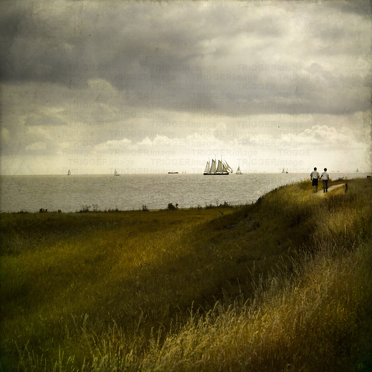 man and woman walking along a path by the sea with tall ships in the distance under a grey sky