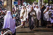 11 JULY 2013 - PATTANI, PATTANI, THAILAND:  Women walk to the Pattani Central Mosque in Pattani, Thailand, Thursday night for Ramadan services. The mosque is one of the busiest in south Thailand. About 15,000 people attend nightly Ramadan services in the mosque. Ramadan is the ninth month of the Islamic calendar, and the month in which Muslims believe the Quran was revealed. Muslims believe that the Quran was sent down during this month, thus being prepared for gradual revelation by Jibraeel (Gabriel) to the Prophet Muhammad. The month is spent by Muslims fasting during the daylight hours from dawn to sunset. Fasting during the month of Ramadan is one of the Five Pillars of Islam.     PHOTO BY JACK KURTZ