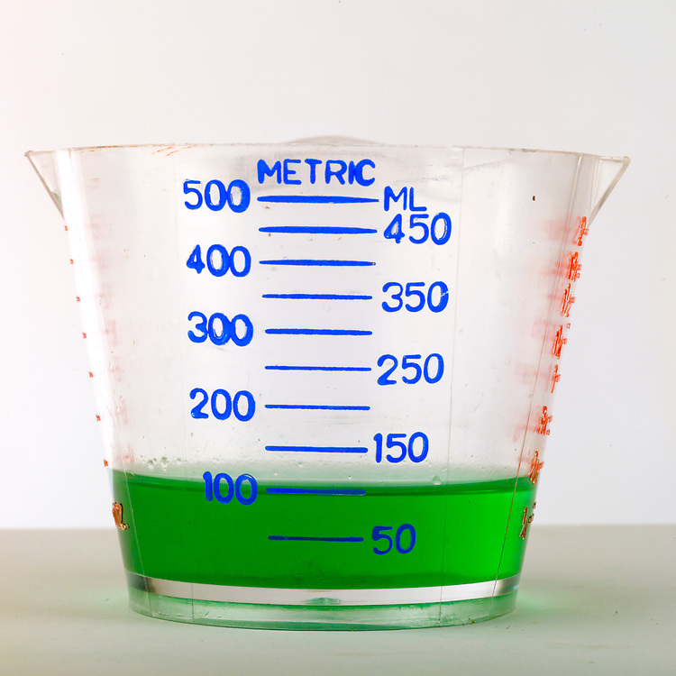 Volumes of liquid being measured in a measuring cup.