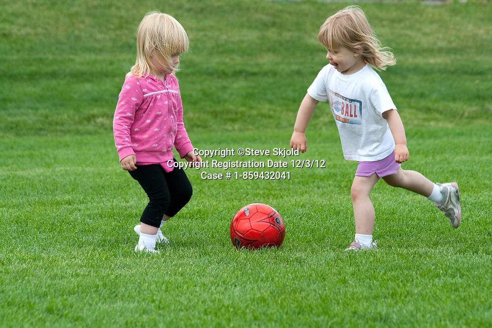 A couple of girls age 2 playing soccer on the field. Carondelet Field by Expo School St Paul Minnesota MN USA